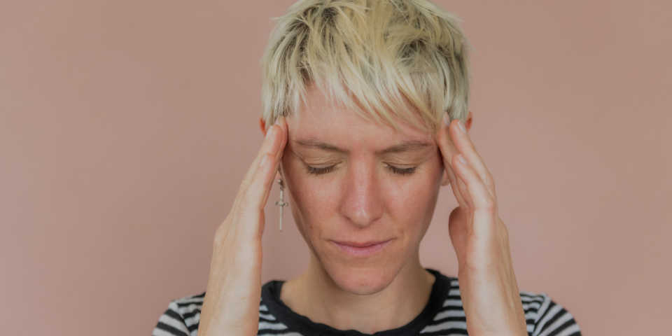 photo of a stressed woman holding her head
