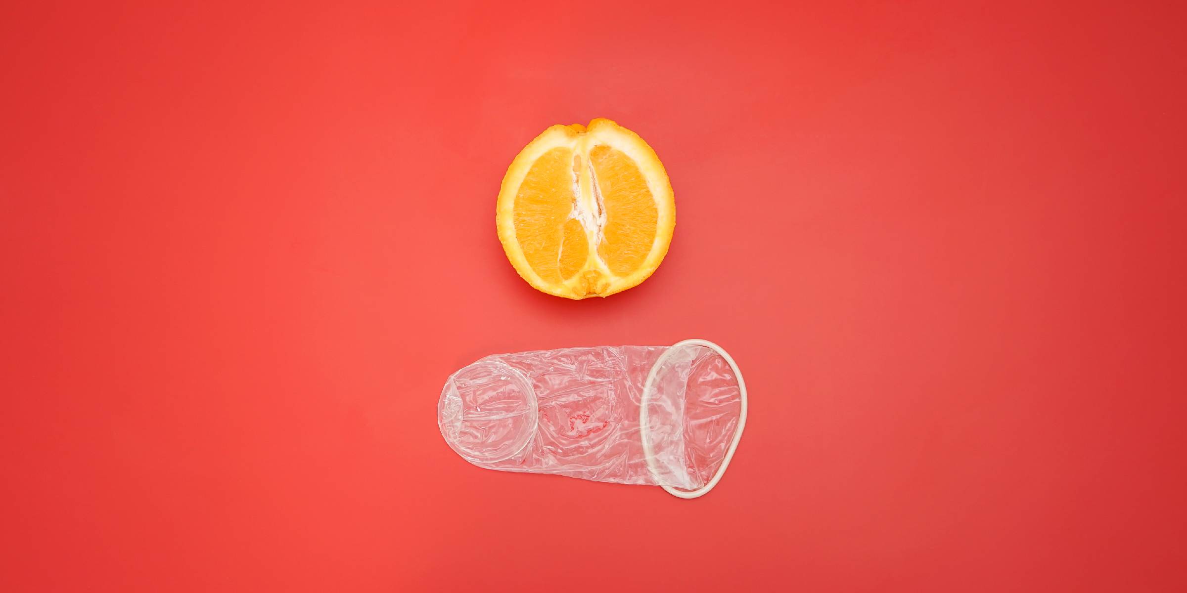 An unpacked female condom, shown next to an orange for size perspective.