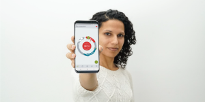 photograph of a woman holding a phone with the clue app opened into the camera