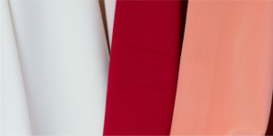 close-up photo of 3 fabric stripes colored red white and apricot