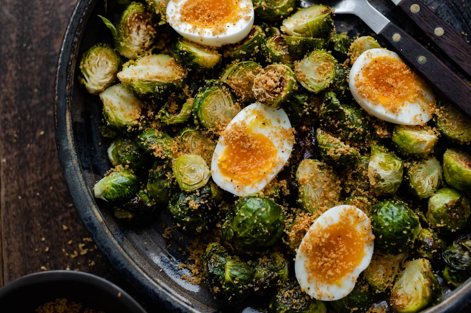 This simple side-dish is made by mixing roasted brussel sprouts, garlic, breadcrumbs, and olive oil together. The dish features jammy organic hard-boiled eggs. | peteandgerrys.com