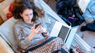 Teenager in bed with phone and laptop