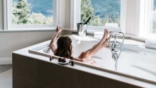 Woman in bathtub in a room with a view