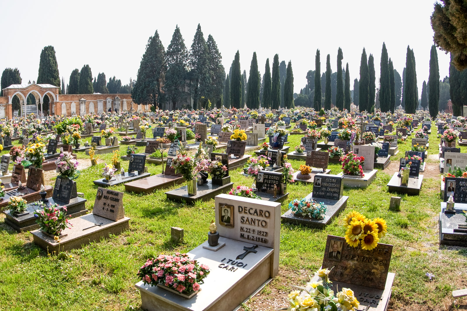 Headstones adorned with flowers in the Isola di San Michele cemetery in Venice, Italy; graveyard; tombstone.