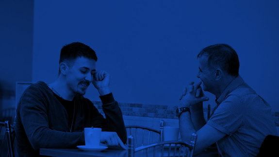 Two people sat in a coffee shop, deep in conversation