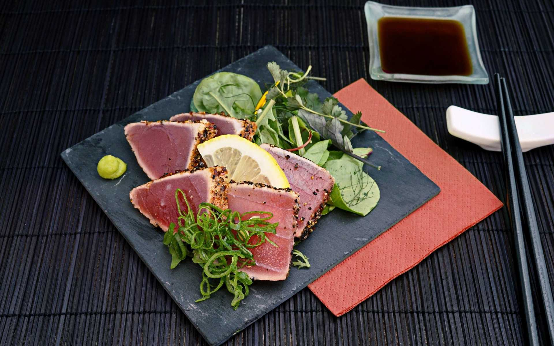 Fancy plate of seared ahi tuna salad on black dish, dark placemat and chopsticks, and bowl of soy sauce