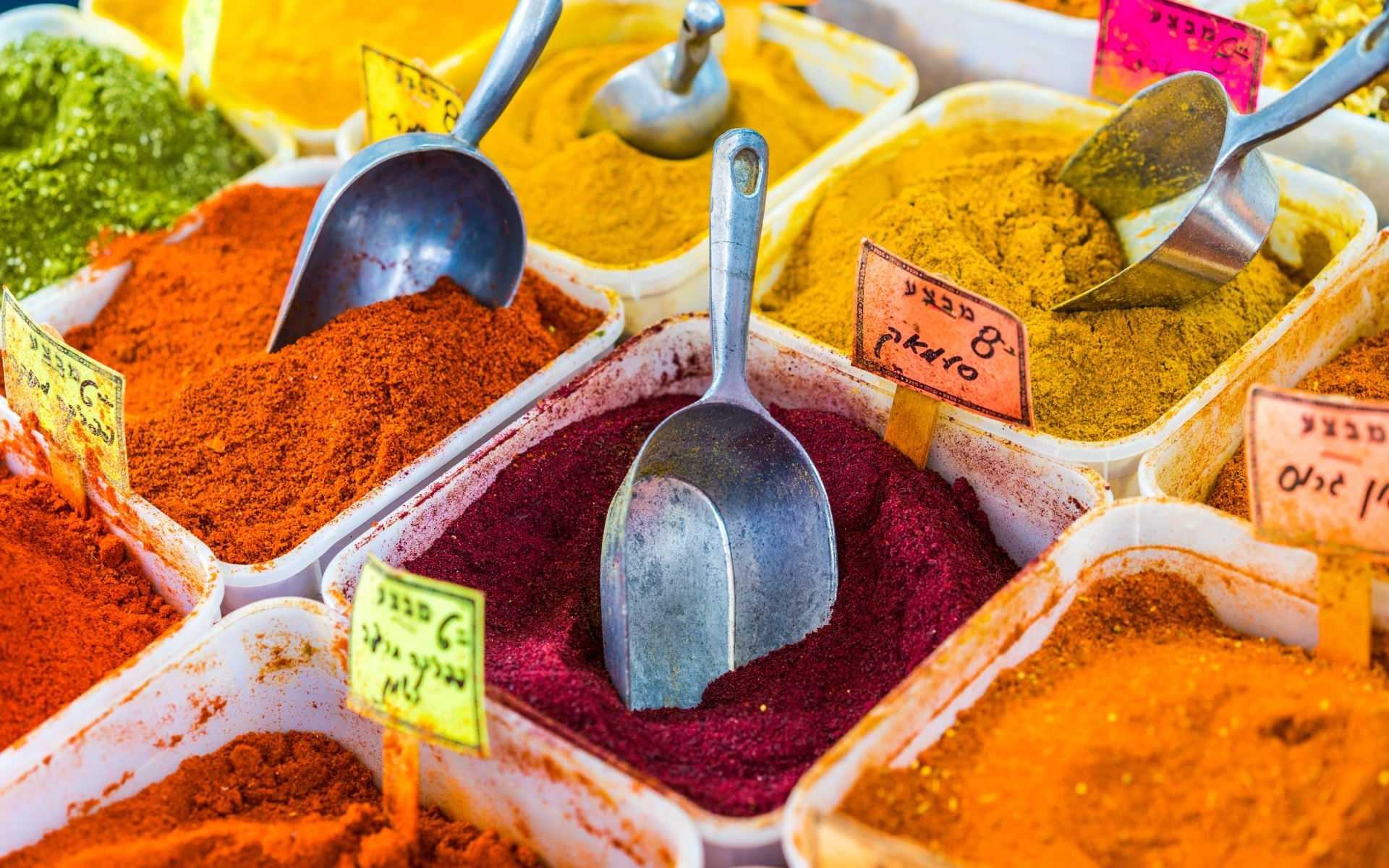 Open bins of colorful red, orange, yellow, and green spices with scoops and price tags