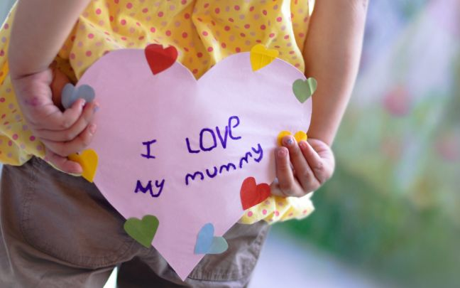 "A child holding a heart-shaped sign that reads ""I love my mummy"" behind their back"