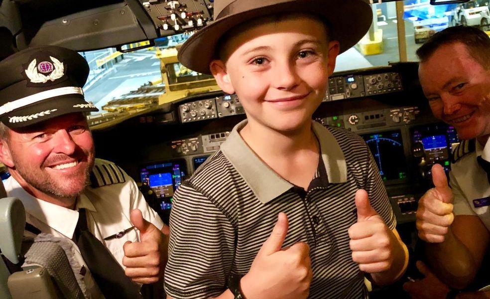Angus Copelin-Walters smiles in the flight deck of a Virgin Australia plane