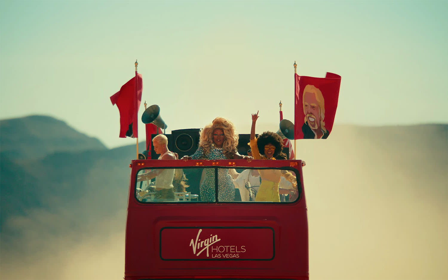 An open top red bus driving through the Las Vegas desert with people partying on the top deck and flags with Richard Branson's face on. The destination on the bus reads: Virgin Hotels Las Vegas