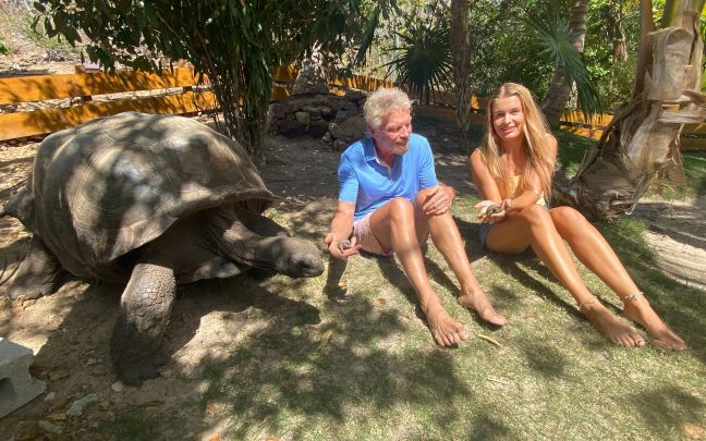 Richard Branson sits with a Giant Tortoise and a Baby Giant Tortoise on Necker Island