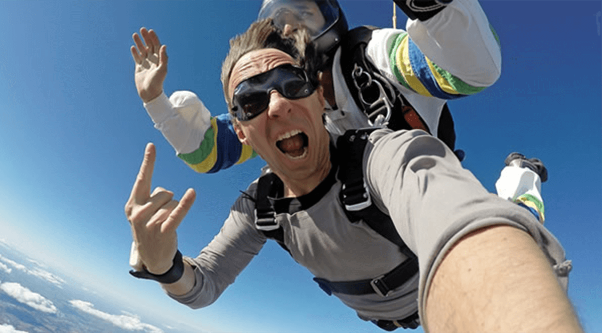 A man does a tandem skydive for charity