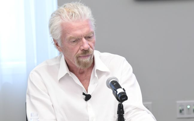 Richard Branson sitting in front of a microphone looking pensive