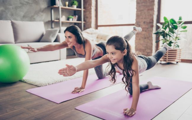 A woman and her daughter practising yoga at home