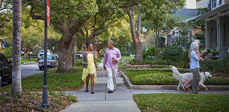 four people walking on the sidewalk in a residential neighborhood