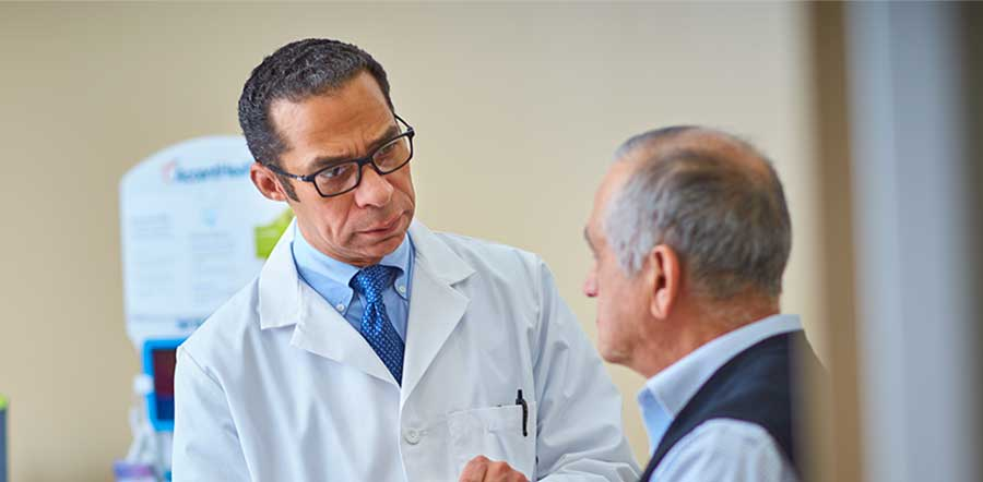 医生与老年男性病人在检查室谈话