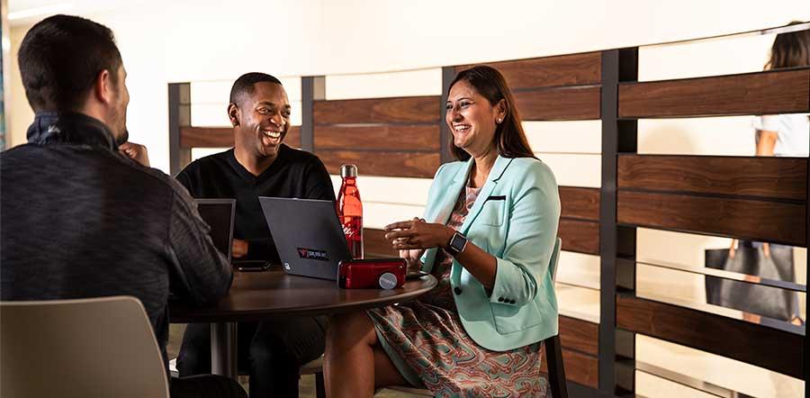 三个人拿着笔记本电脑笑在餐厅的桌子上