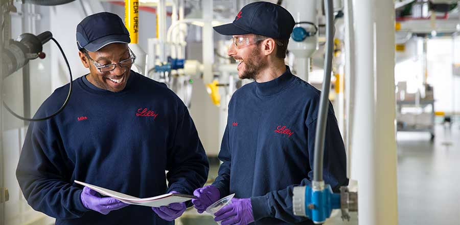 two people smiling looking at paper in manufacturing