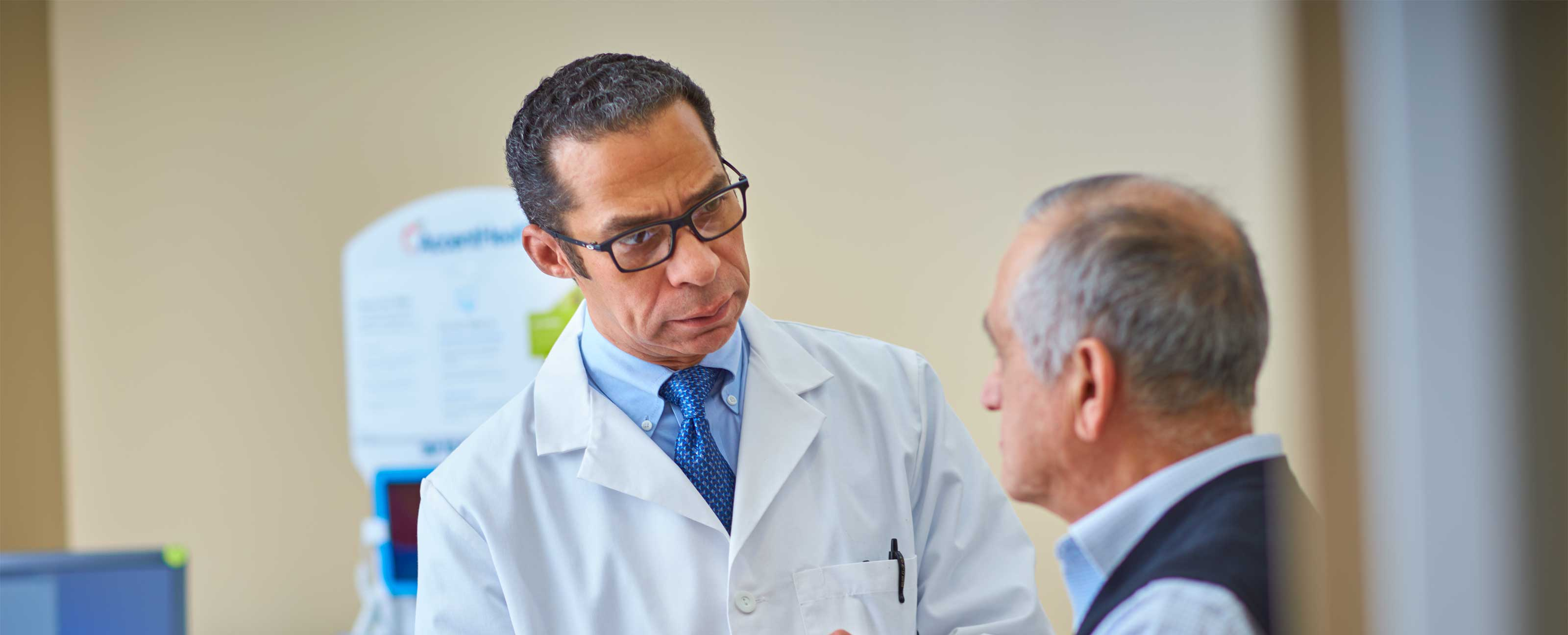 doctor talking to elderly male patient in exam room