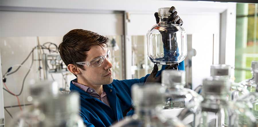 male scientist with goggles looking at glass jar
