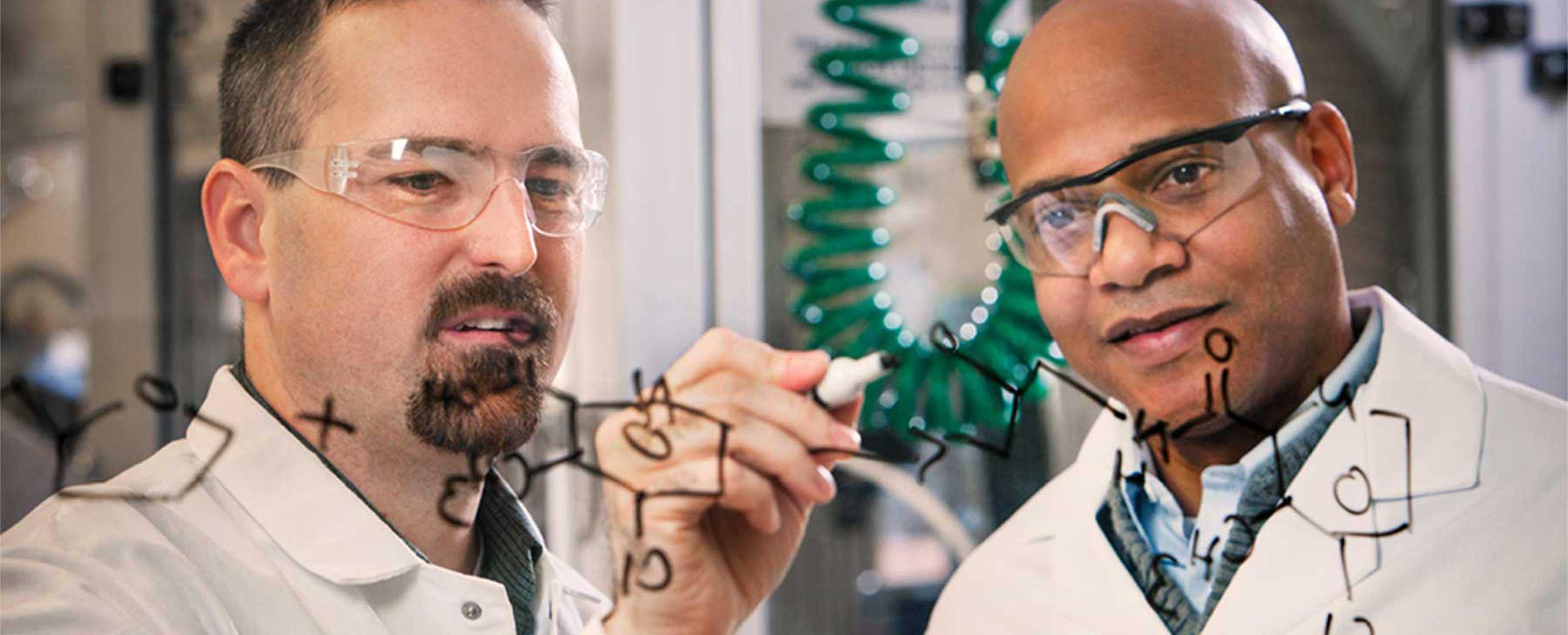 两位科学家在玻璃板上写