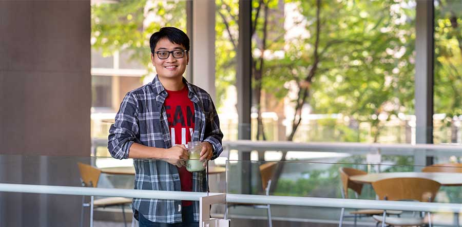 Lilly scientist, Yuan Shi, standing on a patio holding a smoothie