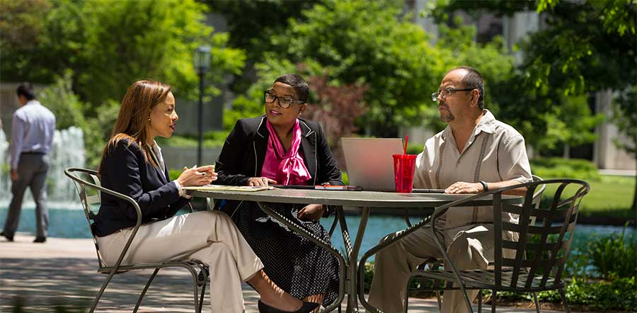 three people sitting outside in lilly courtyard