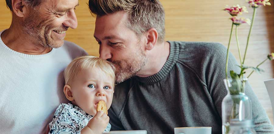 baby being kissed by dad at breakfast table