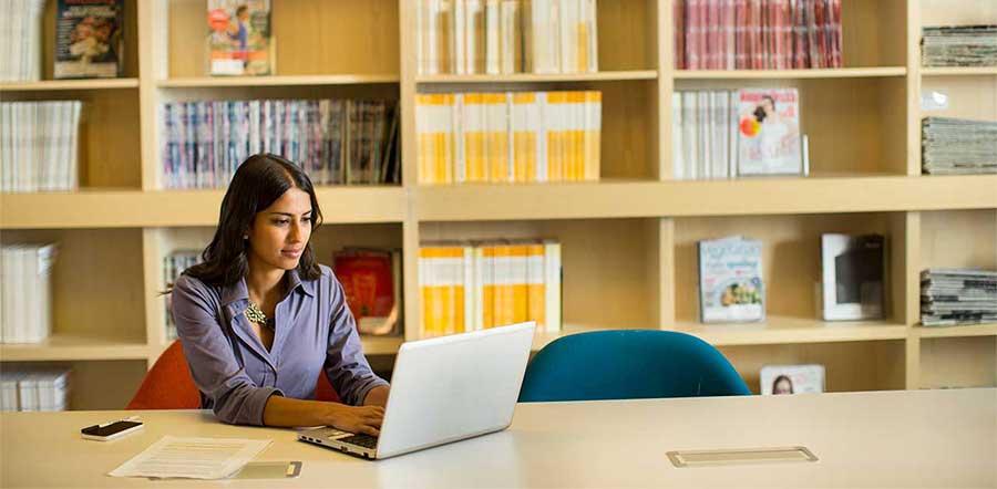 坐在图书馆的笔记本电脑上工作的女士