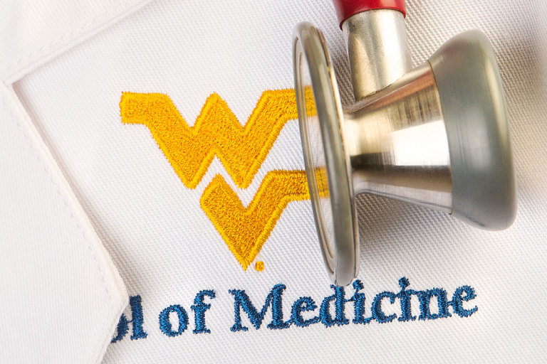 Stethescope over School of Medicine logo on white lab coat