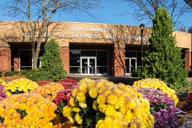Colorful fall mums and the main entrance of the College of Business and Economics buildling