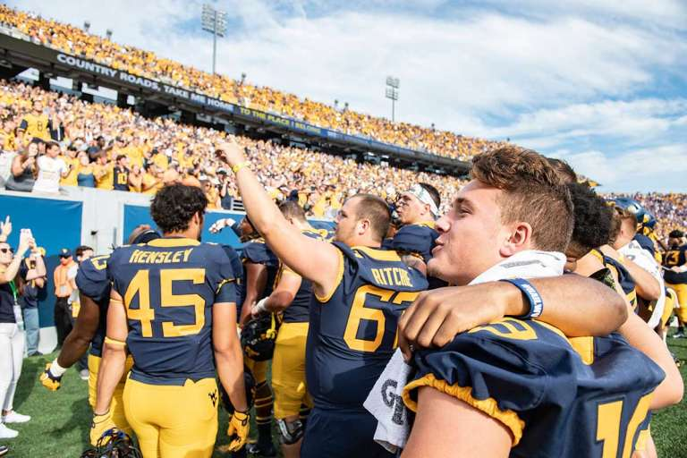 Football players join the student section to sing 'Take Me Home, Country Roads' at Milan Puskar Stadium