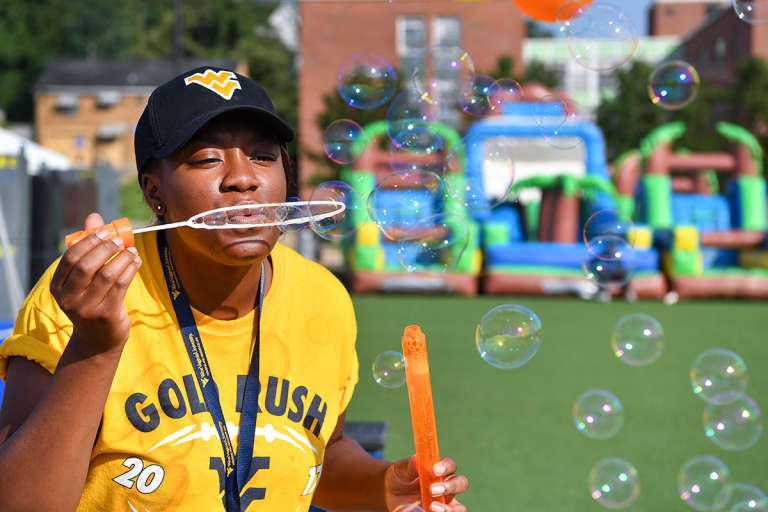 Female student blows bubbles at an event on Mountainlair Plaza