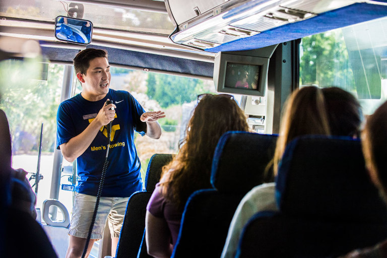 WVU tour guide uses microphone to speak to visitors on tour bus