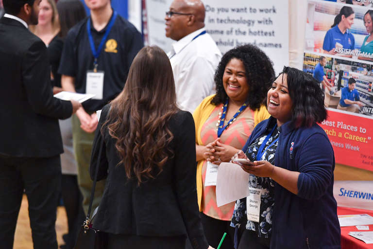 A student talks to Sherwin Williams representatives at a career fair