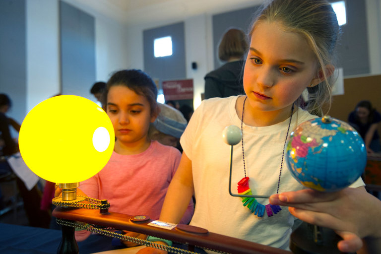 Children examine a model of the solar system