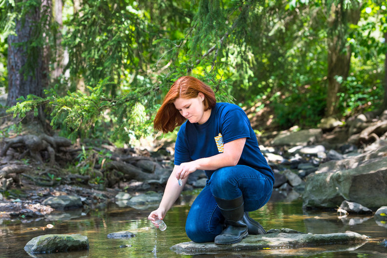 Taking water sample from stream