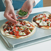 Baking pizzas on the back of a baking sheet makes it easier to remove the pizzas from the pan without bending them. Don't overload the tortillas with toppings.