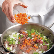 Brown the ground beef in butter, breaking up meat with a wooden spoon, then add vegetables.