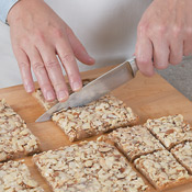 Loosen the foil from edges, then slide cookie off the foil onto a cutting board. Trim edges (<em>optional</em>); cut into eighths, then quarter each eighth to make 32 bars.