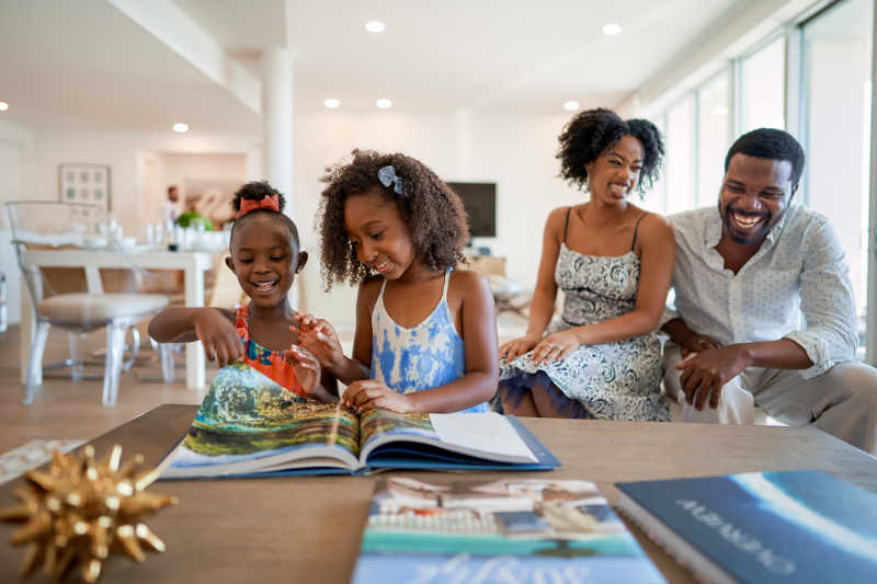 A family has fun together looking through a book in the living room.