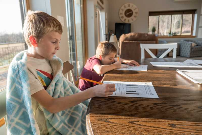Photo of two children doing homework at the dining table.