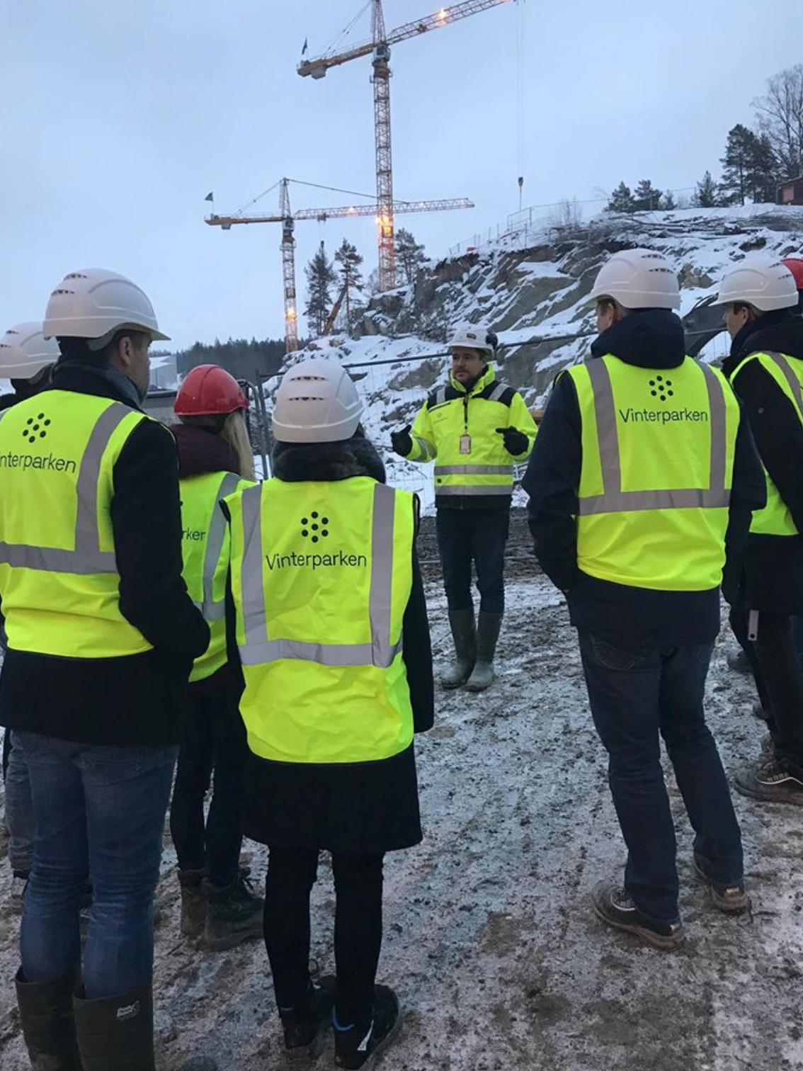 A team of people standing ouside looking at a building site