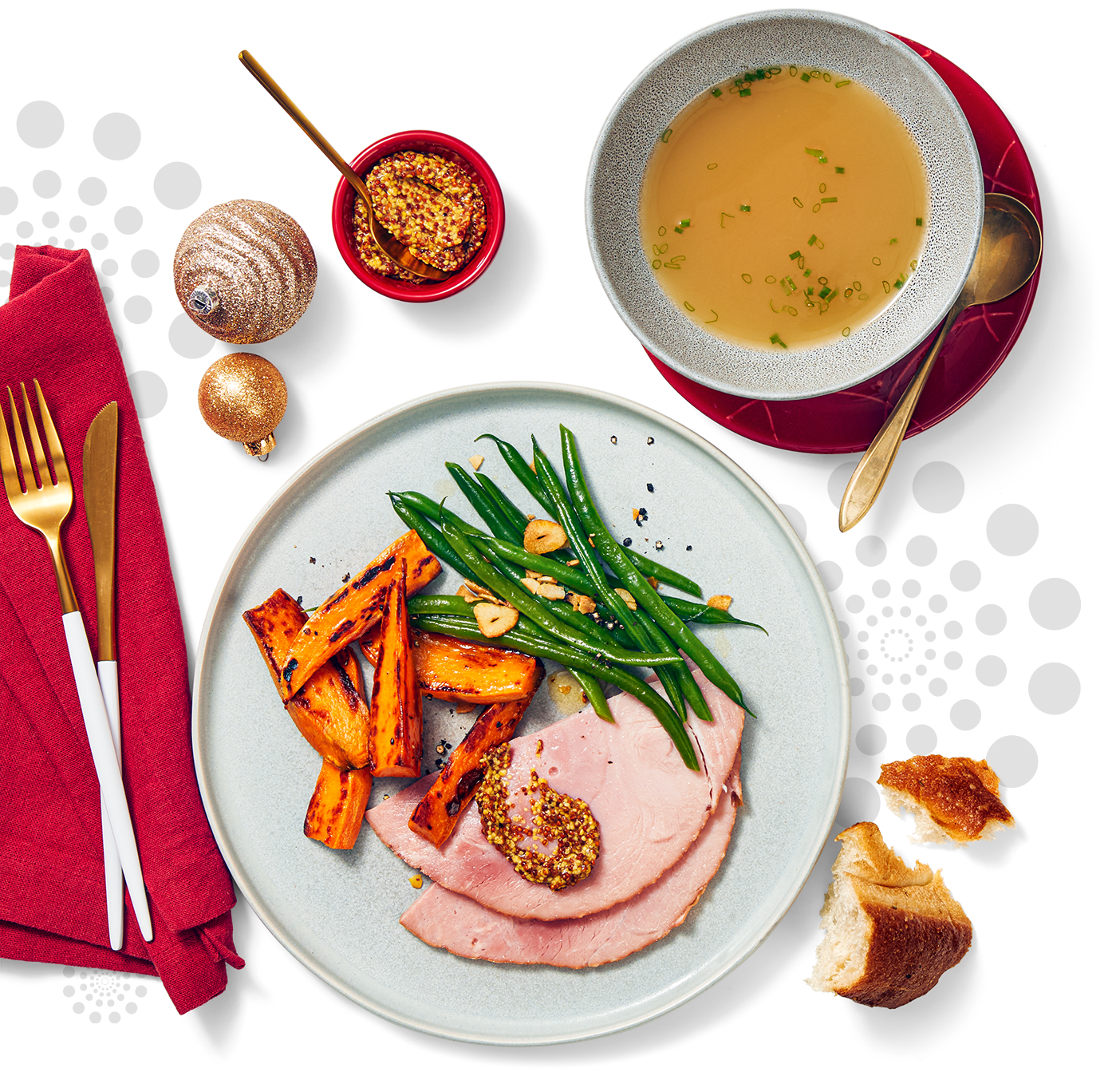A charging plate with a healthy holiday serving of ham string beans and candied yam slices alongside is a bowl of soup and decorated with a few Christmas ornaments