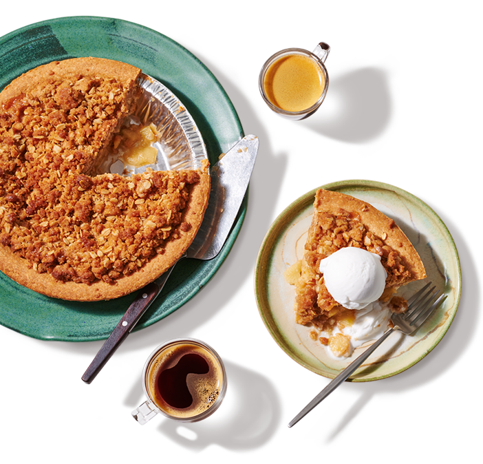A Plant-based apple crumble ready to be served with one piece removed plated and served a la mode on with 2 hot beverages.