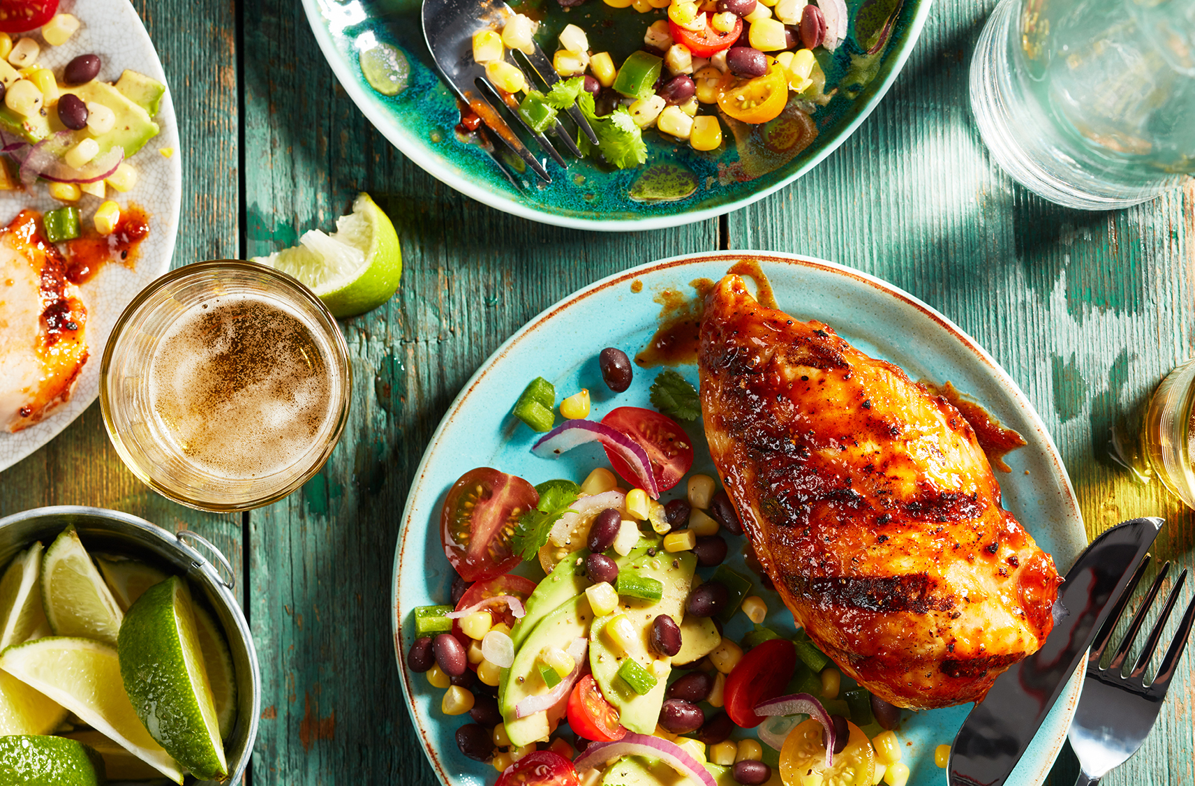 grilled pablano lime chicken served with corn a black bean salad all on a light blue plate.  lime wedges and a glass of drink on the side