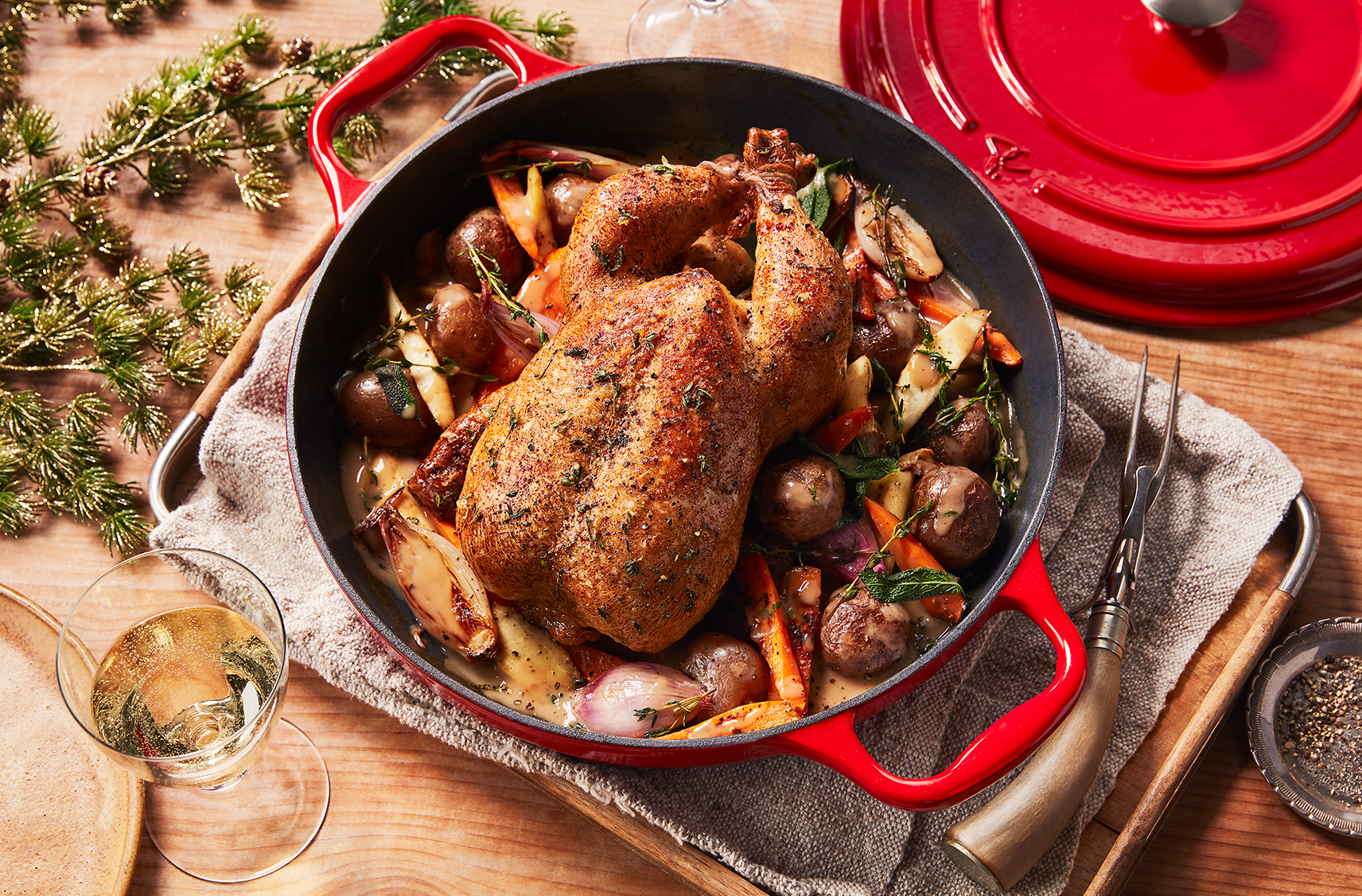 A Dutch stock pot filled with a roasted chicken and root vegetables on a table top with the dutch pot lid off to the side and a sparkling beverage