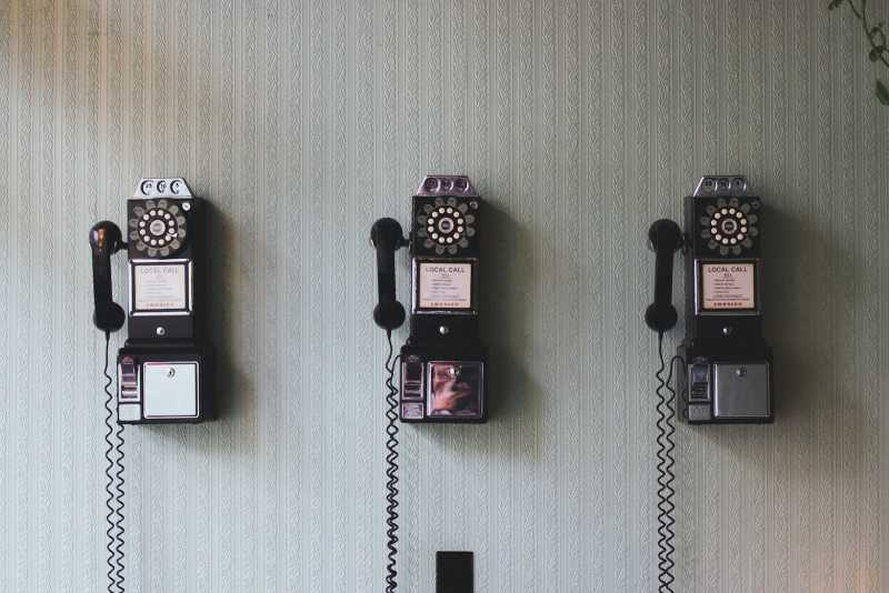 A group of three vintage telephones lined up against a wall.
