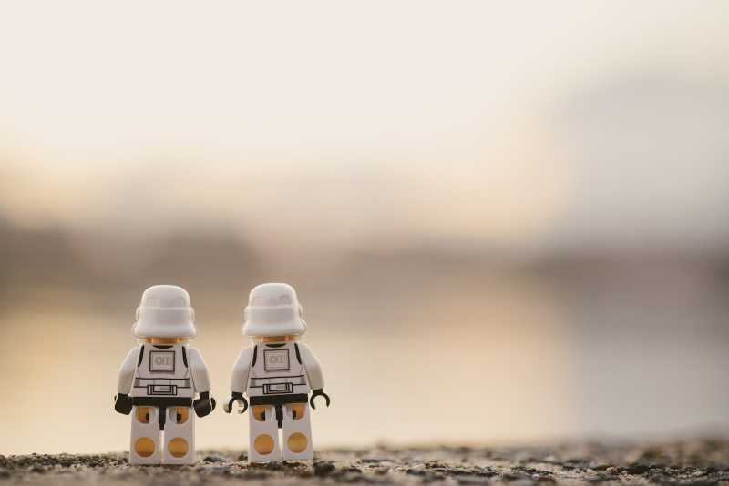 Two Lego minifigures standing close to each other and looking off into the distance.