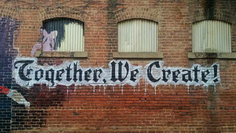 A brick wall spray painted with the words, Together we create!